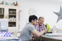 Son helping senior father paying bills at laptop — Stock Photo