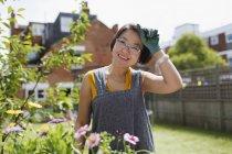 Porträt lächelnde Frau bei der Gartenarbeit im sonnigen Hof — Stockfoto