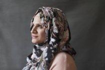 Serene, thoughtful woman wearing floral hijab, looking away — Stock Photo