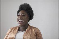 Безтурботна жінка, сміючись від стіни — стокове фото