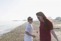 Heureux couple lesbien sur la plage ensoleillée — Photo de stock