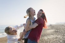 Lesbian couple and daughter laughing on sunny beach — Stock Photo