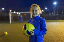 Ritratto fiducioso ragazza calciatore sul campo di notte — Foto stock