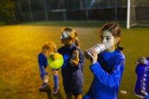 Jogadora de futebol fazendo uma pausa, bebendo água no campo à noite — Fotografia de Stock