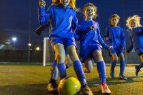 Equipe de futebol meninas praticando em campo à noite — Fotografia de Stock