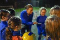 Дівчина футболістів слухати тренера в туляться — стокове фото