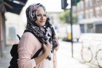 Portrait confident woman in floral hijab on urban sidewalk — Stock Photo