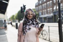 Portrait smiling, confident woman with smart phone wearing floral hijab on urban sidewalk — Stock Photo