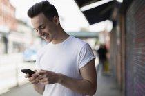 Souriant adolescent garçon à l'aide de téléphone intelligent sur le trottoir urbain — Photo de stock