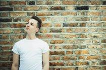 Adolescent réfléchi debout au mur de briques — Photo de stock