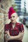 Portrait confiant jeune femme mohawk rose sur trottoir urbain — Photo de stock