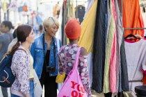 Jovens amigas fazendo compras na calçada urbana — Fotografia de Stock
