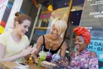 Молодые женщины-друзья наслаждаются коктейлями в кафе на тротуаре — стоковое фото