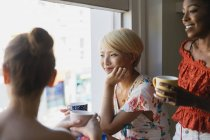 Young women friends drinking coffee at apartment window — Stock Photo