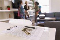 Ключи от дома и договор на стол в аренду дома — стоковое фото