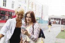 Jovens amigas enviando mensagens com telefone inteligente na rua urbana — Fotografia de Stock