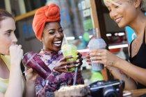 Молоді жінки друзі, пили коктейлі на тротуарі кафе — стокове фото