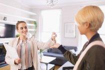 Immobilienmakler übergibt Frau Schlüssel in Wohnung — Stockfoto