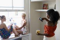 Молода жінка з камерою телефону фотографування друзів, сидячи в квартирі вікна — стокове фото