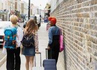 Молодые женщины с чемоданами и рюкзаком ходят по городскому тротуару — стоковое фото