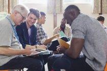 Hombres leyendo documentos en terapia de grupo en centro de comunidad - foto de stock