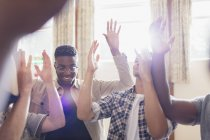 Men praying with arms raised in prayer group — Stock Photo