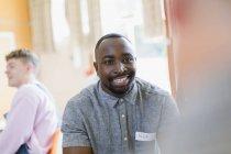 Sourire jeune homme à l'écoute en thérapie de groupe — Photo de stock