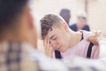 Homem reconfortante chateado adolescente no aconselhamento — Fotografia de Stock