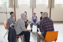 Men talking in group therapy circle — Stock Photo