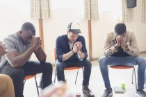 Men praying with rosaries in prayer group — Stock Photo