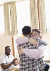 Men hugging in group therapy — Stock Photo