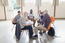 Men talking in circle in group therapy — Stock Photo