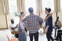 Uomini ne e che applaude in terapia di gruppo nel centro comunitario — Foto stock
