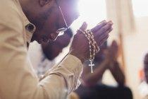 Homem orando com rosário em grupo de oração — Fotografia de Stock