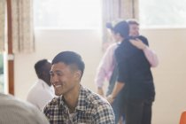 Smiling man enjoying group therapy — Stock Photo