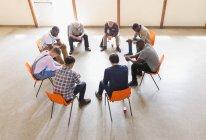 Men praying in circle in prayer group — Stock Photo