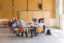Uomini che pregano con le braccia alzate in gruppo di preghiera nel centro comunitario — Foto stock