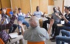 Uomini che pregano con le braccia alzate in gruppo di preghiera — Foto stock
