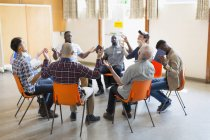 Men praying with arms raised in circle in prayer group — Stock Photo