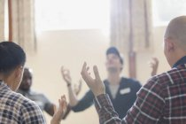 Men with arms raised praying in prayer group in community center — Stock Photo