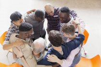 Men hugging in huddle in group therapy — Stock Photo