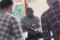 Attento giovane con la Bibbia in gruppo di preghiera — Foto stock