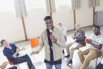 Man with microphone leading group therapy — Stock Photo