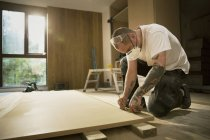 Construction worker with tattoos measuring and marking wood board in house — Stock Photo