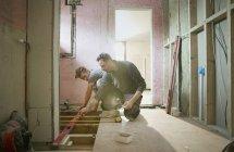 Travailleurs de la construction utilisant l'outil de niveau dans la maison — Photo de stock
