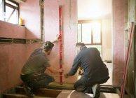 Lavoratori edili che utilizzano strumenti di livello e metro a nastro in casa — Foto stock