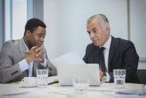 Uomini d'affari che discutono di scartoffie in riunione — Foto stock