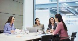 Glückliche Geschäftsfrauen unterhalten sich im Konferenzraum — Stockfoto