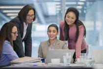 Улыбающиеся деловые женщины, пользующиеся ноутбуком в конференц-зале — стоковое фото