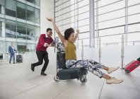 Playful couple running with luggage cart in airport — Stock Photo